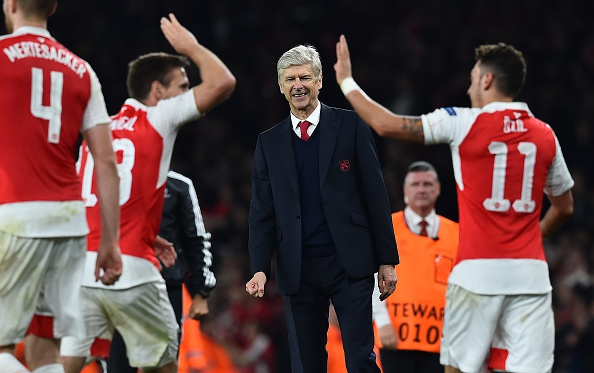 Arsenal's French manager Arsene Wenger (C) watches as Arsenal's German midfielder Mesut Ozil (R) celebrates scoring his team's second goal with teamamte Arsenal's Spanish defender Nacho Monreal during the UEFA Champions League football match between Arsenal and Bayern Munich at the Emirates Stadium in London, on October 20, 2015. Arsenal won the match 2-0. AFP PHOTO / BEN STANSALL (Photo credit should read BEN STANSALL/AFP/Getty Images)